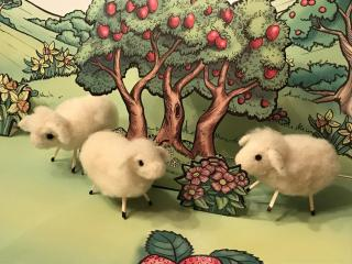 Three needle felted lambs under painted 2D fruit tree images.