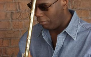 Black male wearing sunglasses holding flute to bowed head.