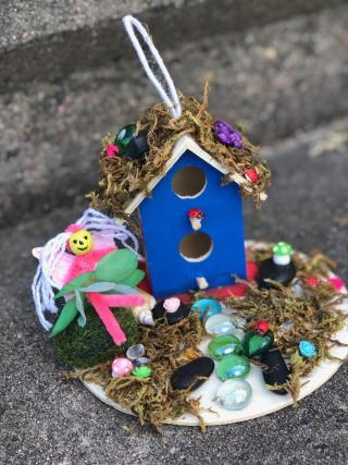 Miniature painted birdhouse with multi-colored glass beads, moss, and doodads.
