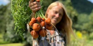 Woman holding bunch of beets freshly harvested.