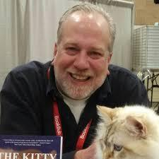 Head and shoulders pic of smiling author with cat and book in foreground on desk.