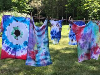 Several recently tie dyed items hanging from a clothes line.